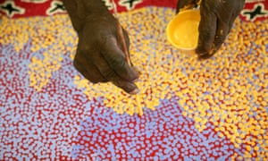 Aboriginal artist working on a dot painting in Alice Springs