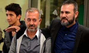 Osama Abdul Mohsen poses with his son Mohamed, and the director of the Spanish football coaching school CENAFE, Miguel Angel Galan after arriving at Atocha train station in Madrid.