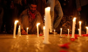 A man lights candles to mourn the victims. pakistan