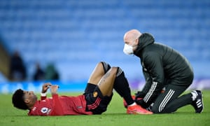 Marcus Rashford receives attention after sustaining an injury.