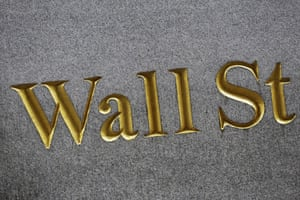 FILE - This Monday, July 6, 2015, file photo shows a sign for Wall Street carved into the side of a building in New York.