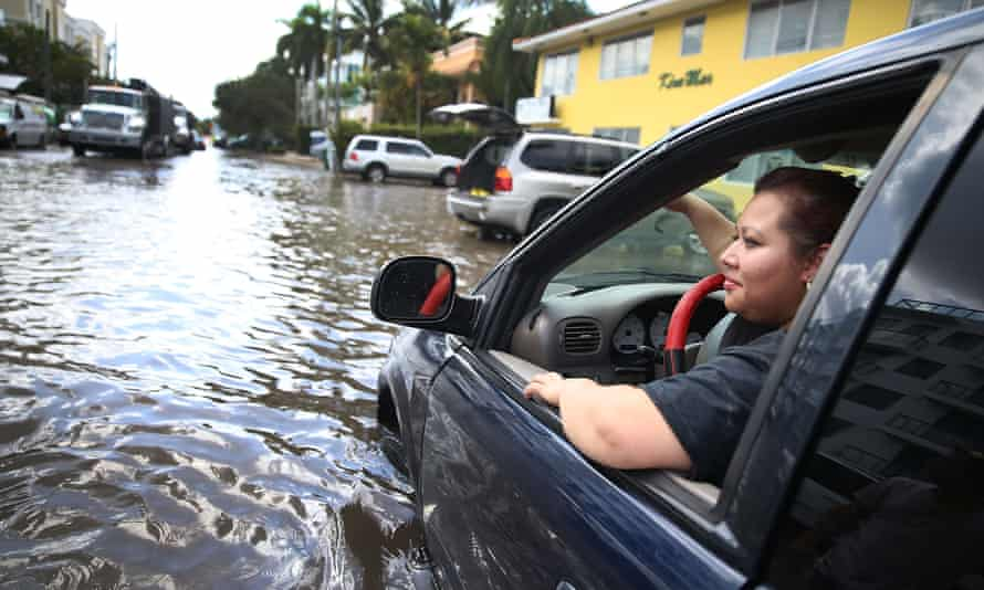 Sandy Garcia sits in her vehicle that was stuck in a flooded street in Fort Lauderdale, Florida. South Florida is among the most vulnerable regions in America to climate change impacts.