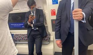 Rishi Sunak travelling on the tube wearing a mask.
