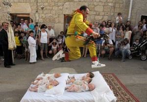 A man representing Satan jumps over six babies during the festival of El Colacho. The rite is supposed to represent the devil taking original sin away from babies.