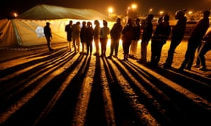 Voters queue to cast their ballots before polls closed outside a polling station in Alexandra township in Johannesburg on Wednesday