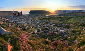 Backpackers admire the midnight sun at Aoalvik Bay, Hornstrandir peninsula, Iceland