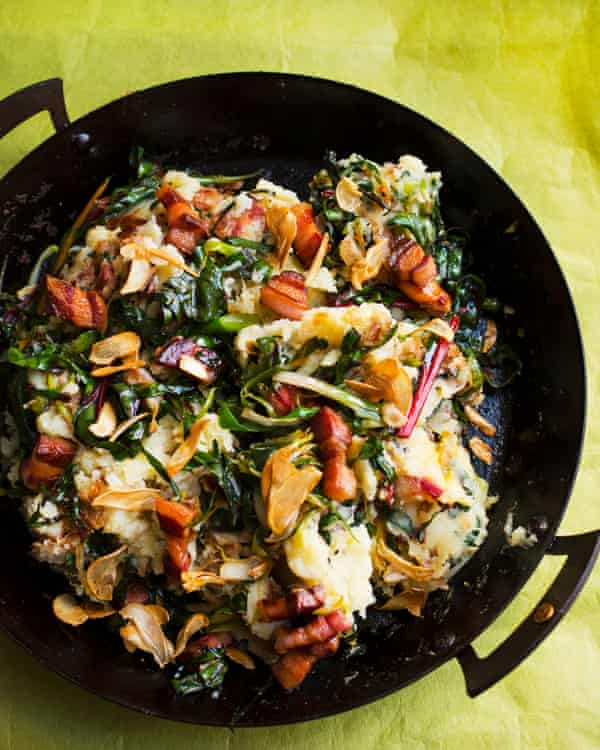 Catalan version of bubble and squeak in a black paella pan with bacon and chard in it