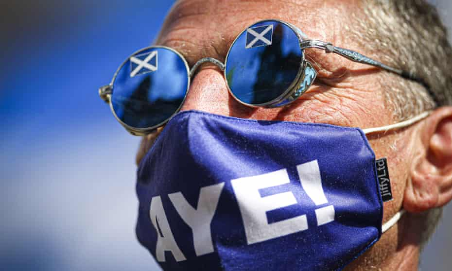 A man in a blue face mask with the word 'Aye!' in big white letters and circular sunglasses with saltire stickers on them