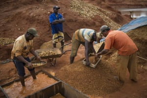 Artisanal miners separate gravel with sieves