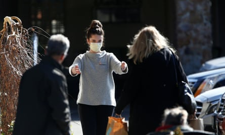 A staff member wearing a mask receives bags of supplies at the Life Care Center of Kirkland.