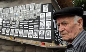 An Ossetian man stands in front of pictures of locals killed during the 2008 South Ossetia conflict.