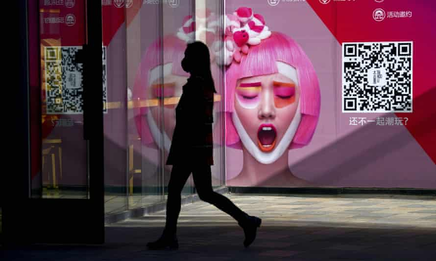 A woman passes a poster ad for a Beijing clothing store.