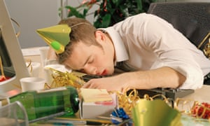 Young man asleep at desk, surrounded by remnants of office party hangover