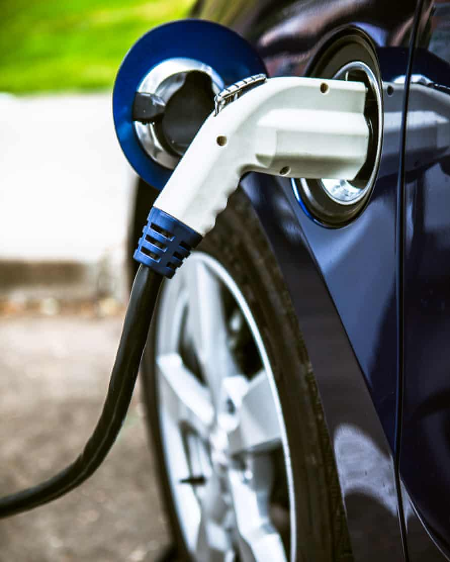 A modern electric car hooked up to a charging terminal has its battery refueled.