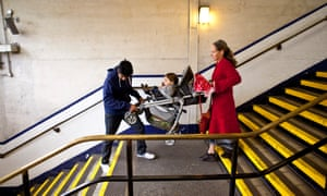 Carrying a push chair down the stairs in a London tube station.