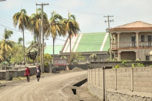 Men walk down a street after eruptions from La Soufrière volcano covered the area with a thick layer of ash in Georgetown.