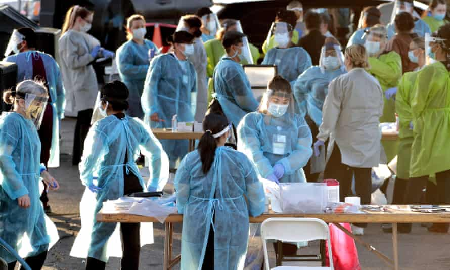 In this photo taken Saturday, June 27, 2020, medical personnel prepare to test hundreds of people lined up in vehicles in Phoenix, Arizona's western neighborhood of Maryvale for coronavirus.