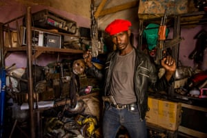 Wakaliwood actor Ronald Kazibwe, alias Sergi, chooses the guns from a weapons workshop he will use in the next scene of a film.