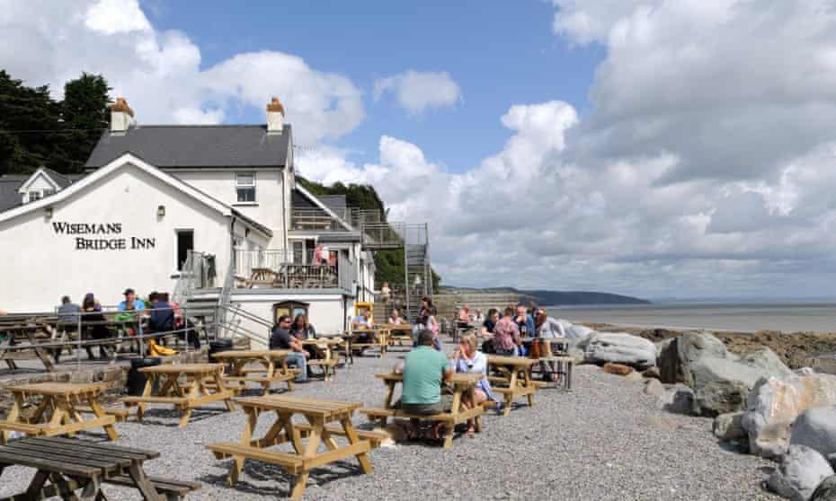 People sitting outside Wisemans Bridge Inn Pembrokeshire Wales Cymru, UK.