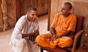 Jay Shetty as a monk in a white robe, talking to a saffron-robed monk