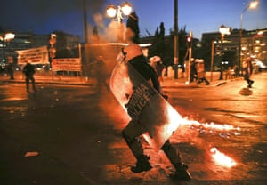Another photograph by Yannis Behrakis shows riot police on the move as they disperse protesters during the clashes in Athens.