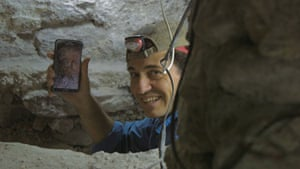 Archaeologist Francisco Estrada-Belli shows his phone to the camera after taking a picture of artefacts discovered in a royal tomb at Holmul