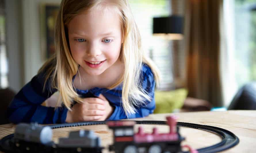 A girl playing with a toy train