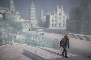 A worker walks past ice sculptures during the annual ice and snow festival in Harbin, China