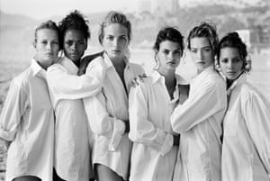Supermodels in white shirts stand sandwiched against each other on a beach