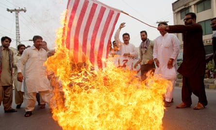 A Pakistani demonstrator holds a burning US flag as others protest against a drone strike in Balochistan.