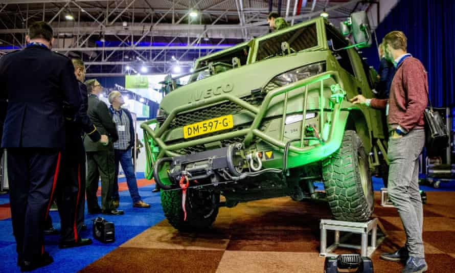 Defense industry professionals look at a military vehicle on display at an arms fair in the Netherlands.