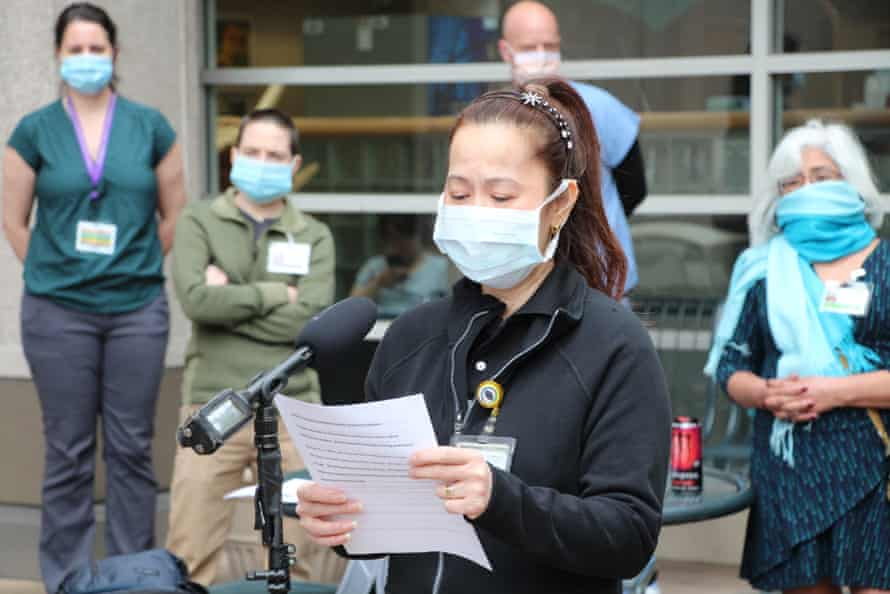 Ma Jesusa Keberenge, a cafeteria worker, presents an employee petition to University of Washington medical center management in April. Workers sought better protections after a Covid-19 outbreak.
