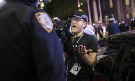 AP journalist Robert Bumsted reminds a police officer that the press are considered 'essential workers'. NYPD officers surrounded, shoved and yelled expletives at him and his co-worker.