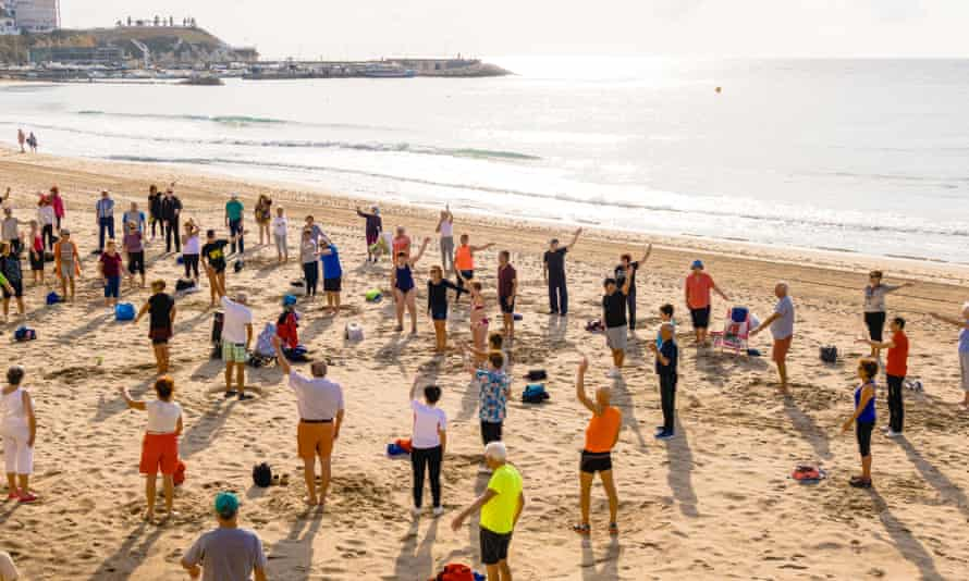 People doing exercises on a beach in Benidorm, Spain.