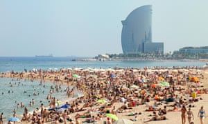 Crowds of people sunbathing on Barceloneta Beach with Hotel W in the background, Barcelona, Spain
