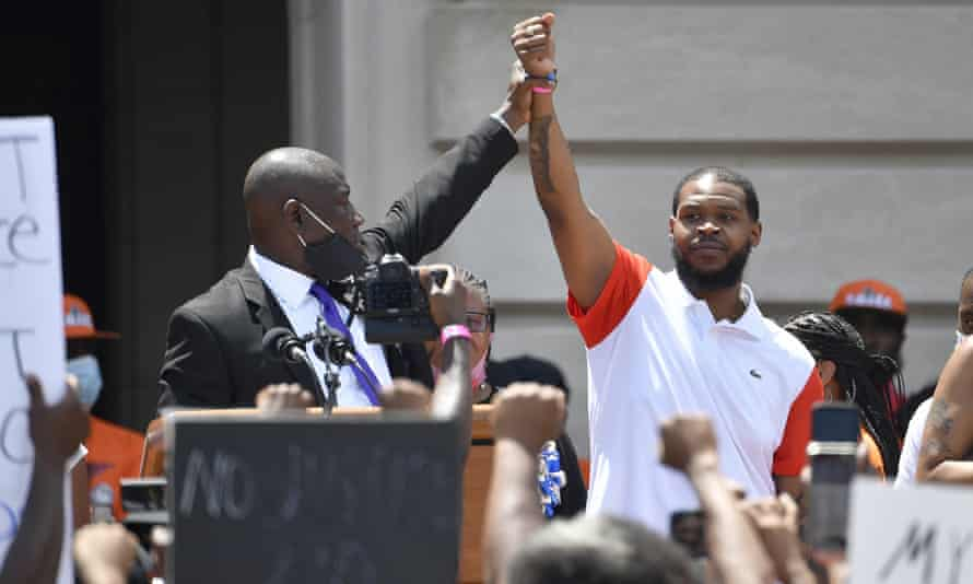 Attorney Benjamin Crump, left, holds up the hand of Kenneth Walker during a rally on the steps of the Kentucky state capitol in Frankfort, Kentucky, on 25 June.