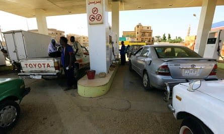 People gather to get fuel at a petrol station in Khartoum, Sudan