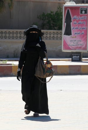 In Raqqa, a woman walks past a billboard that carries a verse from Qur'an urging women to wear a hijab