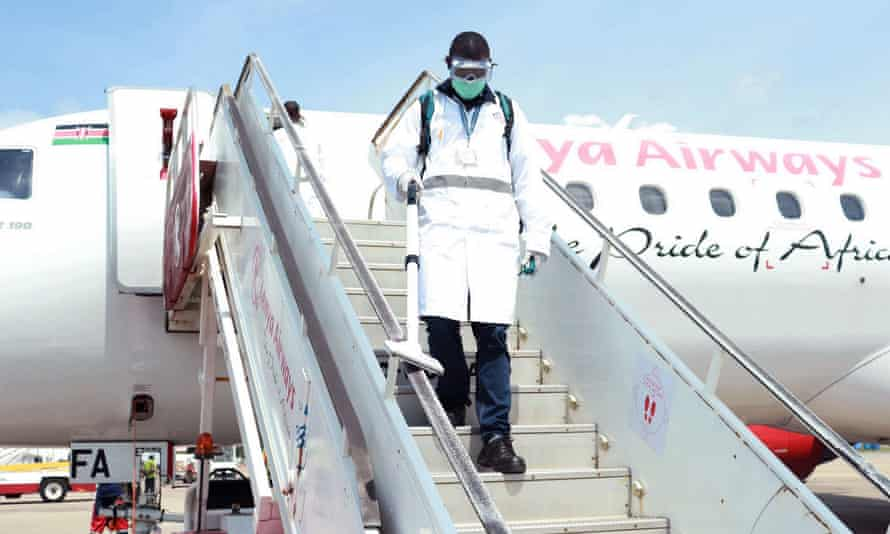 An airport employee disinfects a gangway at Moi International Airport