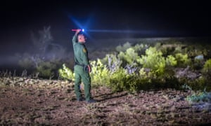 A Border Patrol agent searches the terrain in the Animas mountains in New Mexico's boot heel.