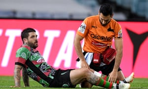 Adam Reynolds of the Rabbitohs receives attention from a trainer after an injury during the game against the Wests Tigers.