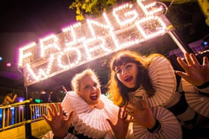 Two women in concertina collars stand in front of a Fringe World sign