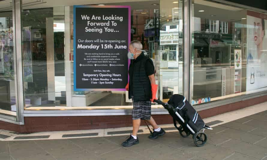 A man with a face mask and rubber gloves and a shopping trolley passes a shop with a sign declaring its reopening date