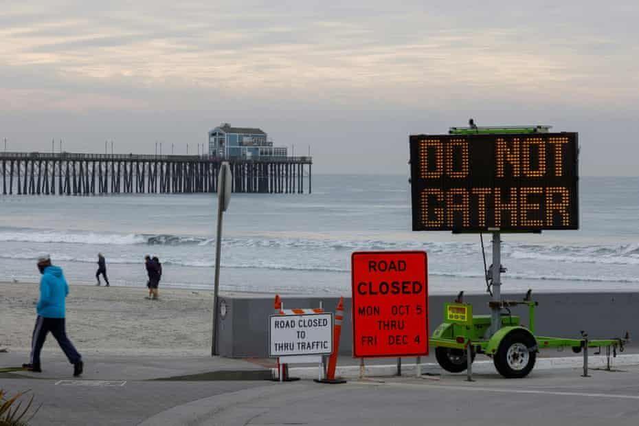 A sign in Oceanside, California, warns against gathering as the new stay-at-home orders take effect.