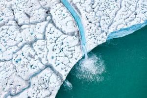 Water runs through the ice into the sea