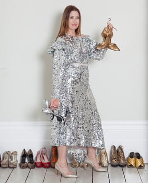 Sharon in a sparkly silver dress and heels holding up a pair of party shoes in each hand and with multiple pairs of shoes lined up behind her