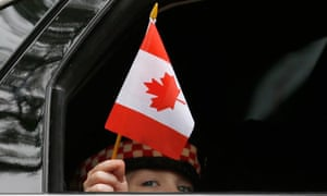 Marcus Cirillo, 5, waves a Canadian flag from a car window as the car leaves following the funeral service for his father