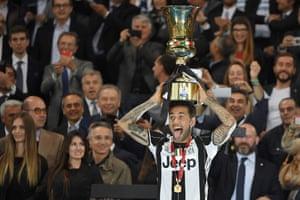 Dani Alves holds the trophy aloft.