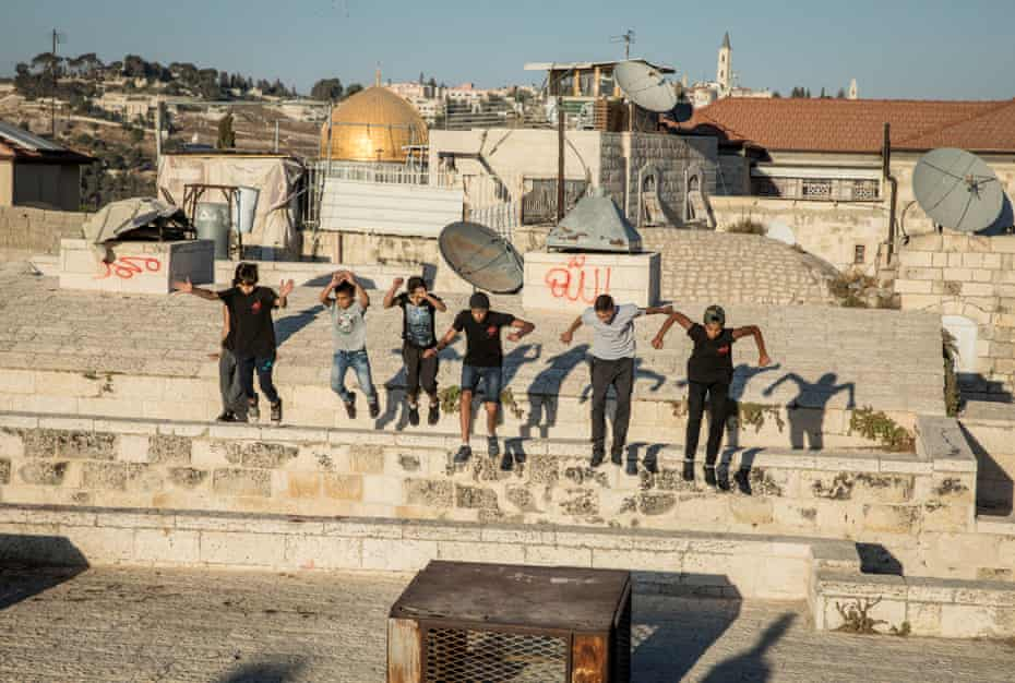 Palestinian boys practice parkour on the Galizia roofs, opposite the Dome of the Rock, in the Old City