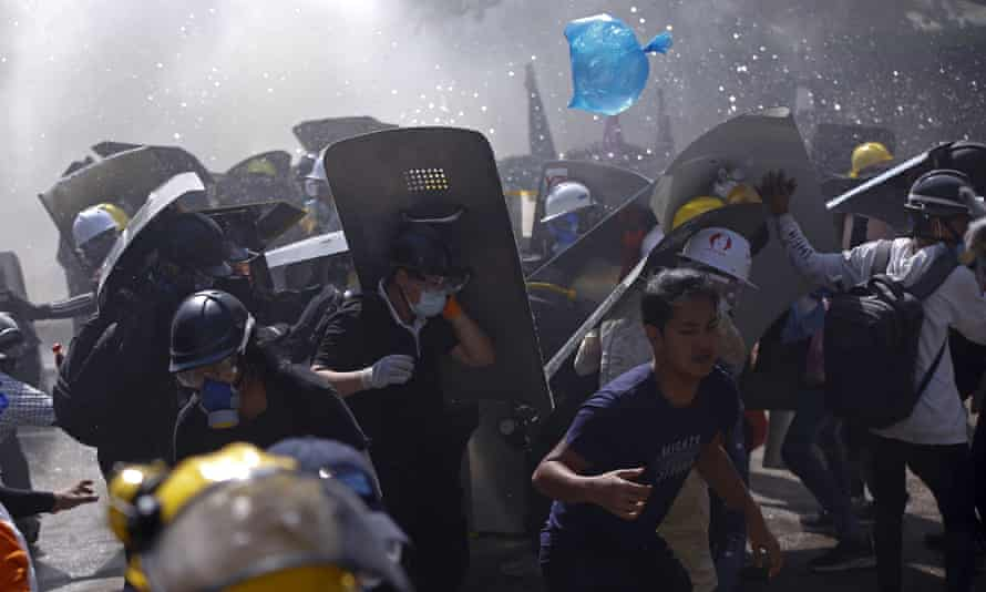 Protesters are dispersed as riot police fire teargas during a demonstration in Yangon on Monday.